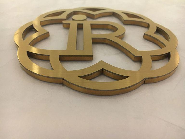Логотип в лифтовом холле из золотой нержавеющей стали